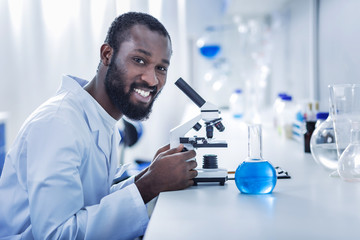 Positive mood. Cheerful nice handsome scientist sitting in front of the microscope and looking at you while enjoying his job
