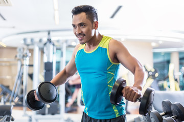 Portrait of a handsome determined young man exercising with dumbbells during upper-body workout routine in a modern fitness club