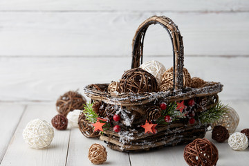 Christmas decorations basket on white wooden background, holiday concept