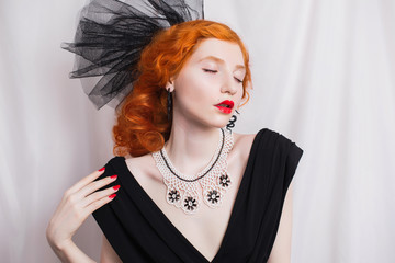 Redhead woman with unusual appearance in black dress and veil on the head and red lips. Girl with pale skin and a beautiful antique necklace on neck and black earrings in the form of snakes.