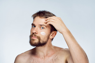 Man with a beard on a light background, cosmetic face cream, beauty, health
