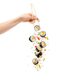 Falling pieces of sushi and sushi roll with wooden chopsticks in female hand, isolated on white background