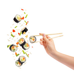 In de dag Sushi bar Falling pieces of sushi and sushi roll with wooden chopsticks in female hand