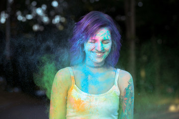 Happy woman with purple hair covered with blue Holi powder at the park