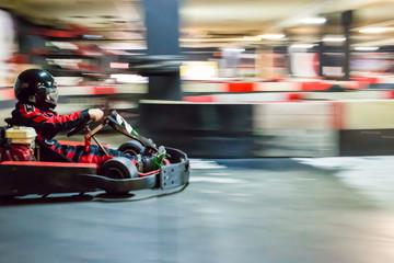 Cart blurred by high speed, a boy having fun - driving fast, racing, speeding.