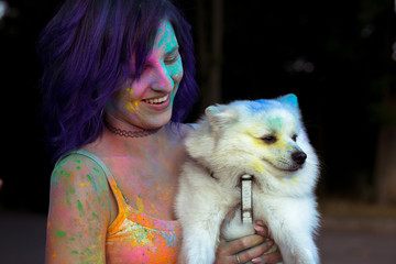 Happy brunette woman with little white dog covered colorful Holi powder