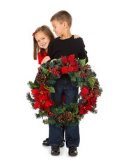 Christmas: Siblings Holding Holiday Wreath And Smiling