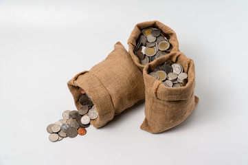 3 sacks of money bags made from hemp sack full with coins isolate on white background with empty copy space.