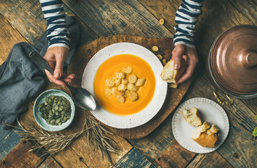 Flat-lay of female hands and Fall warming pumpkin cream soup with croutons and seeds on board over rustic wooden background, top view. Autumn vegetarian, vegan, healthy comfort food eating concept