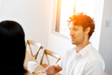 Portrait of man sitting and talking to woman indoors