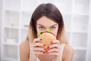 Diet. The concept of healthy and unhealthy nutrition. The model plus size makes a choice in favor of healthy food and fruit by refusing fast food and burger. XXL woman