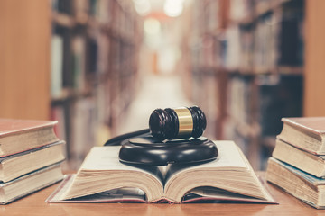 Old book in library with judge gavel on open law textbook in court archive text collection study...