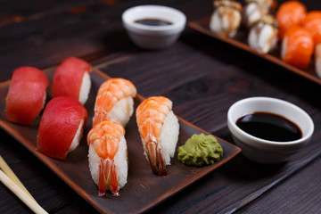 Nigiri sushi set with tuna and prawns served on clay plates, close up. Delicious traditional Japanese food, tasty seafood, sushi restaurant concept