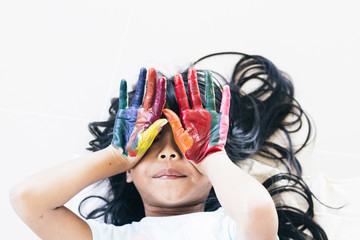 Education , art and creativity learning concept - A black long hair asian student put her colourful hands painting up
