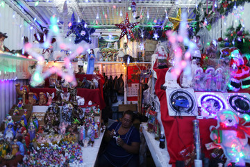 A woman waits for clients at the Christmas market at the Simon Bolivar park in San Salvador