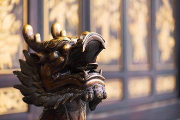 Golden color dragon head scultpure in a buddhist temple, China