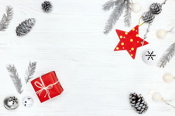 white wooden background with fir tree branches, decorations and gift boxes. winter holidays concept.