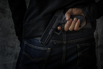 Masked robber with gun aiming into the camera against a black background.