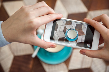 Blogger takes pictures of coffee on table indoor. Close-up hand holding phone mobile taking photo cappuccino