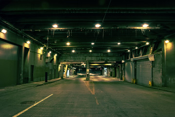 Dark and gritty downtown city street tunnel underpass at night in Chicago.