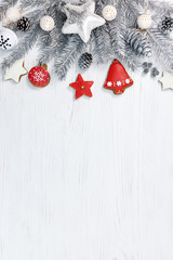 silver christmas fir tree branches with decorations and homemade gingerbreads on white wooden background