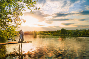 Beautiful summer picture on the nature by the river. A loving couple is standing on the pier on a sunset background.