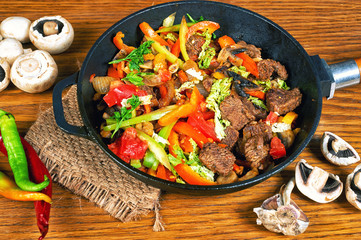 fried meat with vegetables on a wooden table