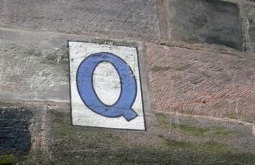 Großbuchstabe Q in blau auf weißem Hintergrund, auf eine Sandsteinwand gemalt