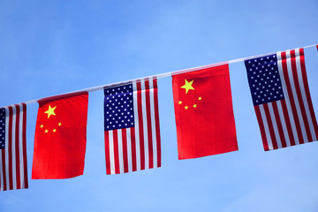 USA and China flags hanging under blue sky