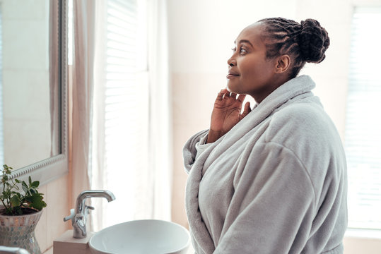 African woman looking at her complexion in a bathroom mirror