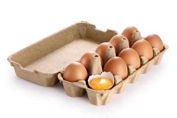 Carton egg box with eggs isolated on white background. Broken egg, yolk.