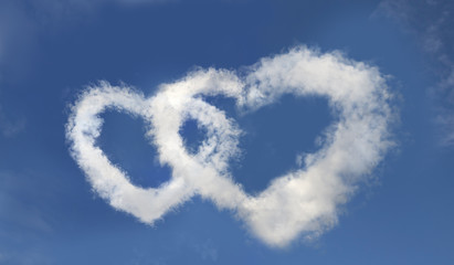 Two hearts made of clouds in the clear blue sky
