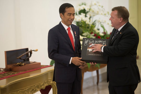Denmark Prime Minister Lars Lokke Rasmussen gives a vinyl record of the heavy metal band Metallica to Indonesian President Joko Widodo after a joint press conference at the Presidential Palace in Bogor