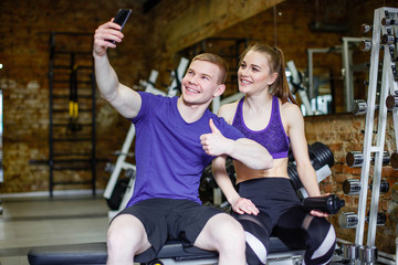 Beautiful happy couple in sportswear doing selfie using smartphone.