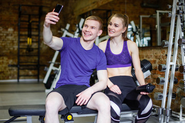 Beautiful happy couple in sports clothes is making selfie using a smart phone and smiling while resting after workout.