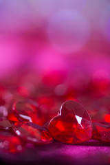 Many red little crystal hearts with bokeh background.