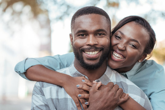 Affectionate young African couple standing outside on a sunny day