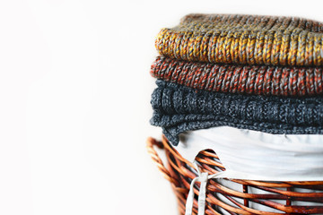 Pile of knitted winter plaids on straw basket isolated on white background. Free copy space.