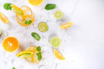 Vitamin summer refreshing drinks. Citrus punch with oranges and lime, with mint sprigs, chilled with ice. On a white marble table, with ingredients, copy space top view