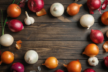 Different fresh onions on wooden table