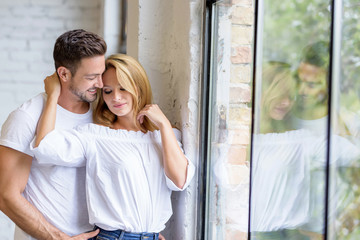 A beautiful young woman standing next to the window with boyfriend hugging her from behind.