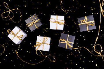 Black and white gift boxes with gold ribbon on shine background. Flat lay.