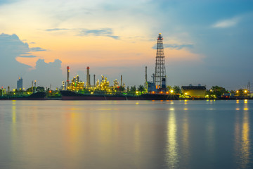 Oil refinery, tanker ship and petrochemical plant at morning time beside Chao Phaya river, Thailand. Smooth water and reflection.
