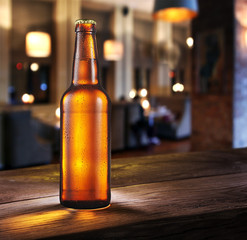 Frosty bottle of light beer on the bar counter.