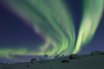 Polar lights over the hills in the winter.