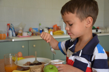 kid eating healthy food at home. Cute little boy is eating a yoghurt. Morning. Breakfast on the table. porridge. healthy food. diet. proper nutrition