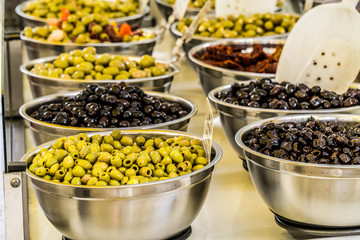 Different cured table olives in the bowls.