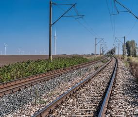 By rail train along wind power plant.