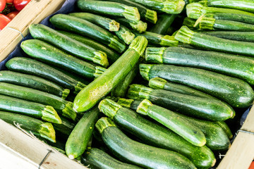 Zucchini or courgette in the wooden crate.