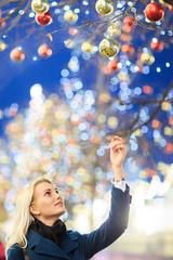 Photo of beautiful woman touching Christmas balls on tree